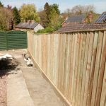 Domestic sleeper retaining wall with close board fencing
